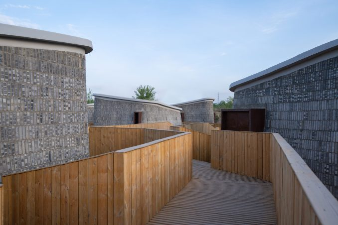 Wooden walkway leading to four vertical pods by AVOID Studio