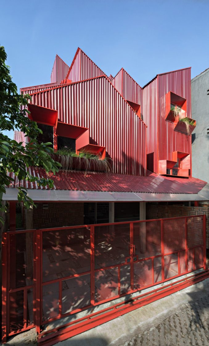 Exterior of red boarding house by Ismail Solehudin Architecture showing stacked volumes