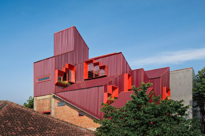 Red stacked boarding house volumes rise above the surrounding rooftops