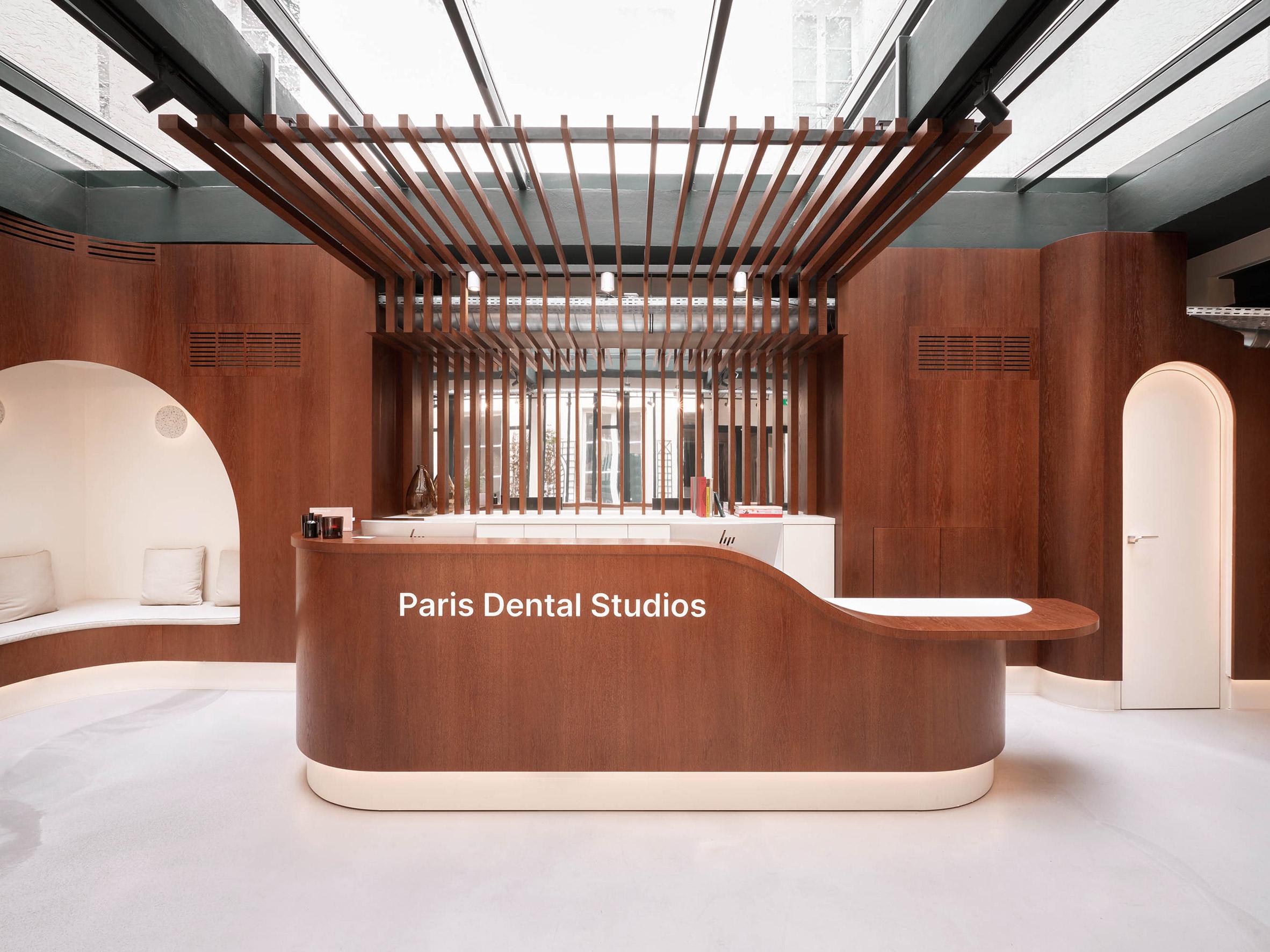 A brown wooden reception desk in Paris Dental Studios