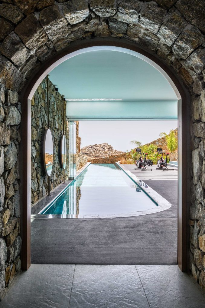 View through stone arch at Mykonos Wellness Resort at exercise bikes next to a pool