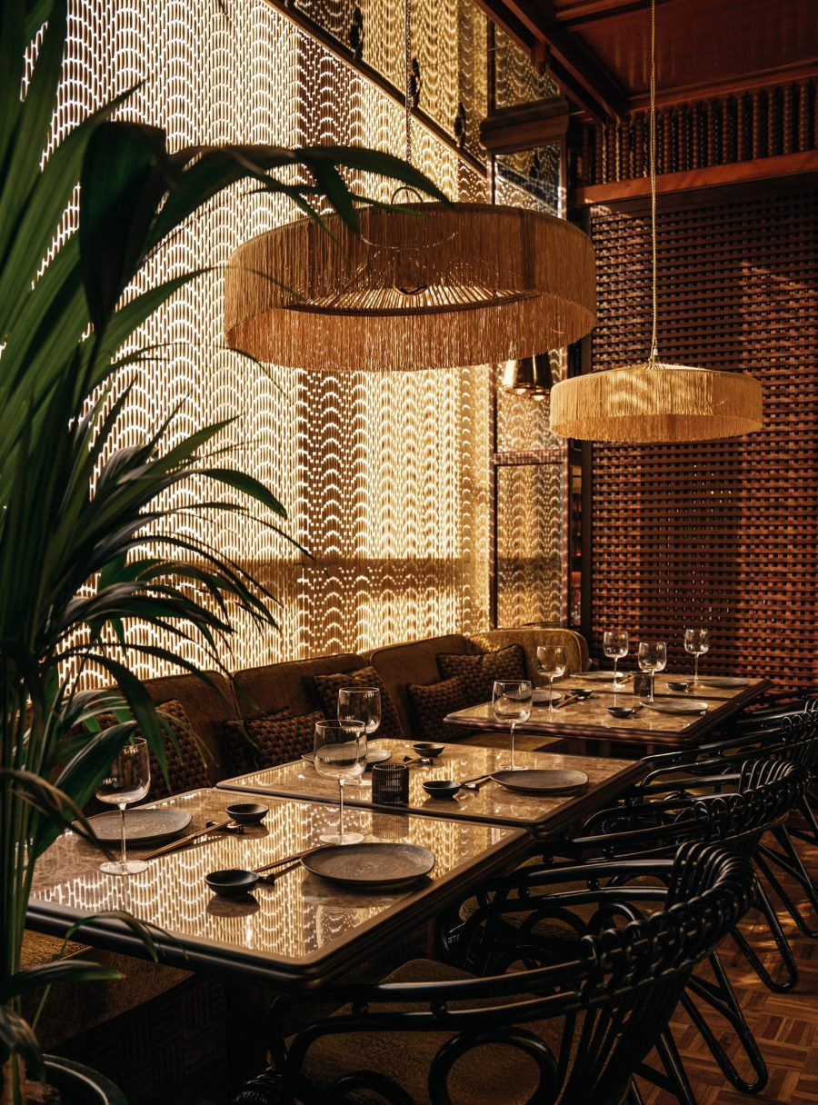 Mimi Kakushi seating area with black cane chairs, wooden bead curtain and tasseled pendant lights