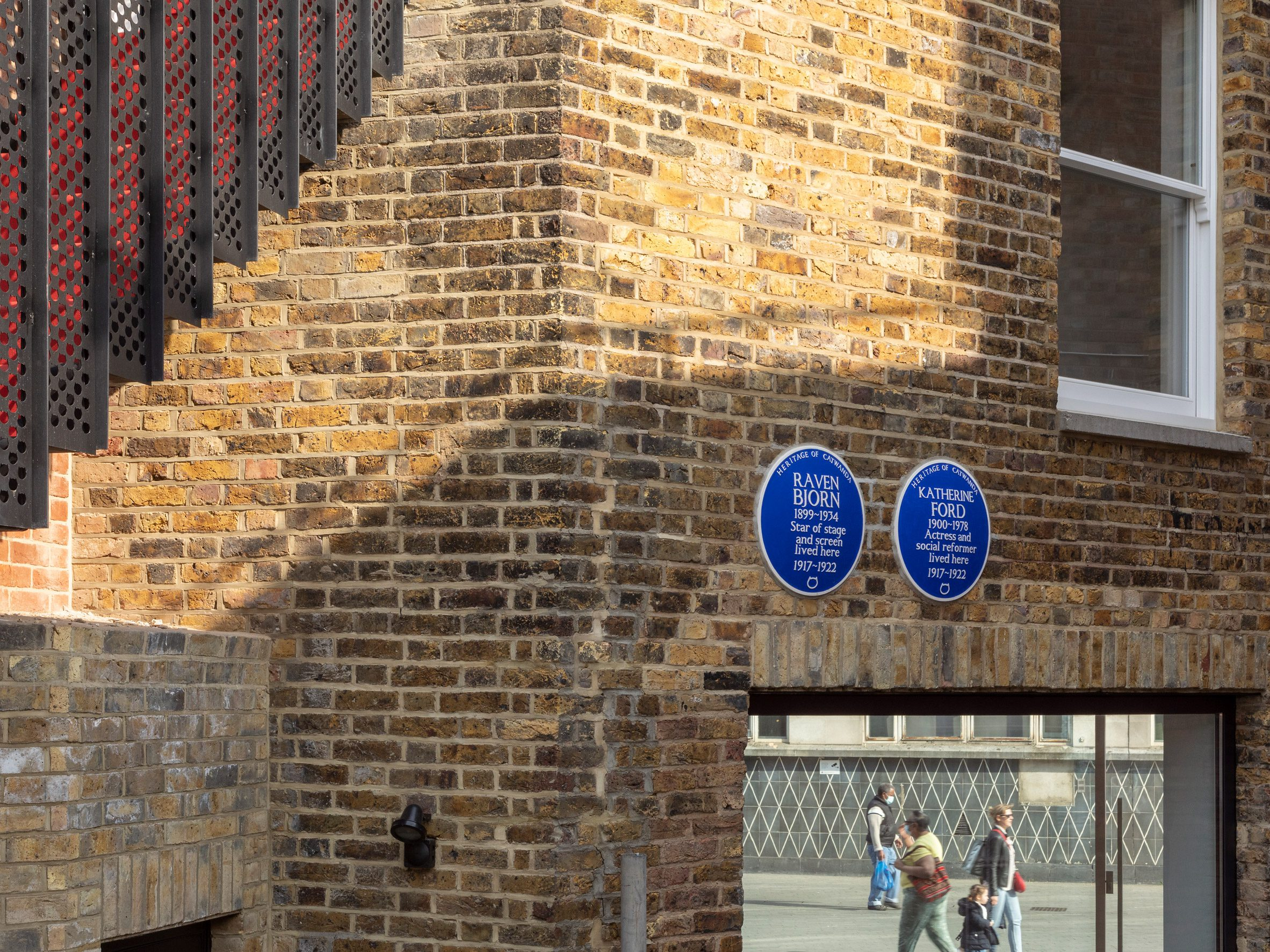 Blue heritage plaques on the exterior of The Queen of Catford by Tsuruta Architects