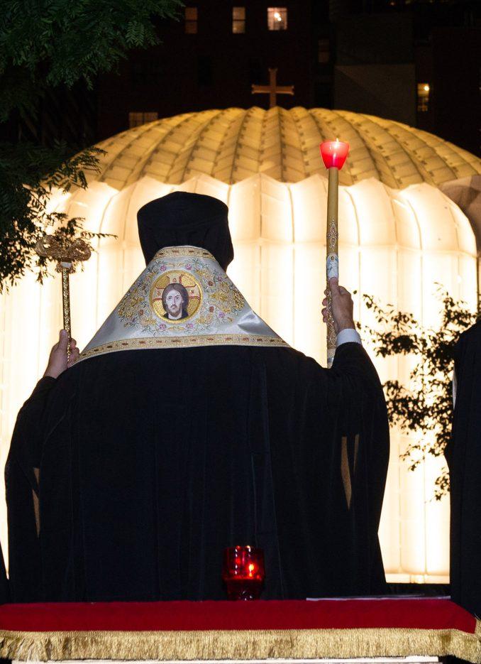 Priest outside illuminated church
