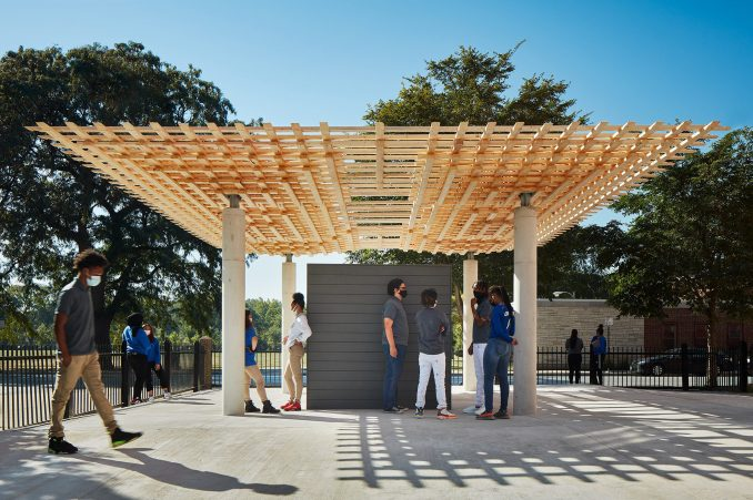 Students stand under the interlocking timber roof of the SPLAM pavilion