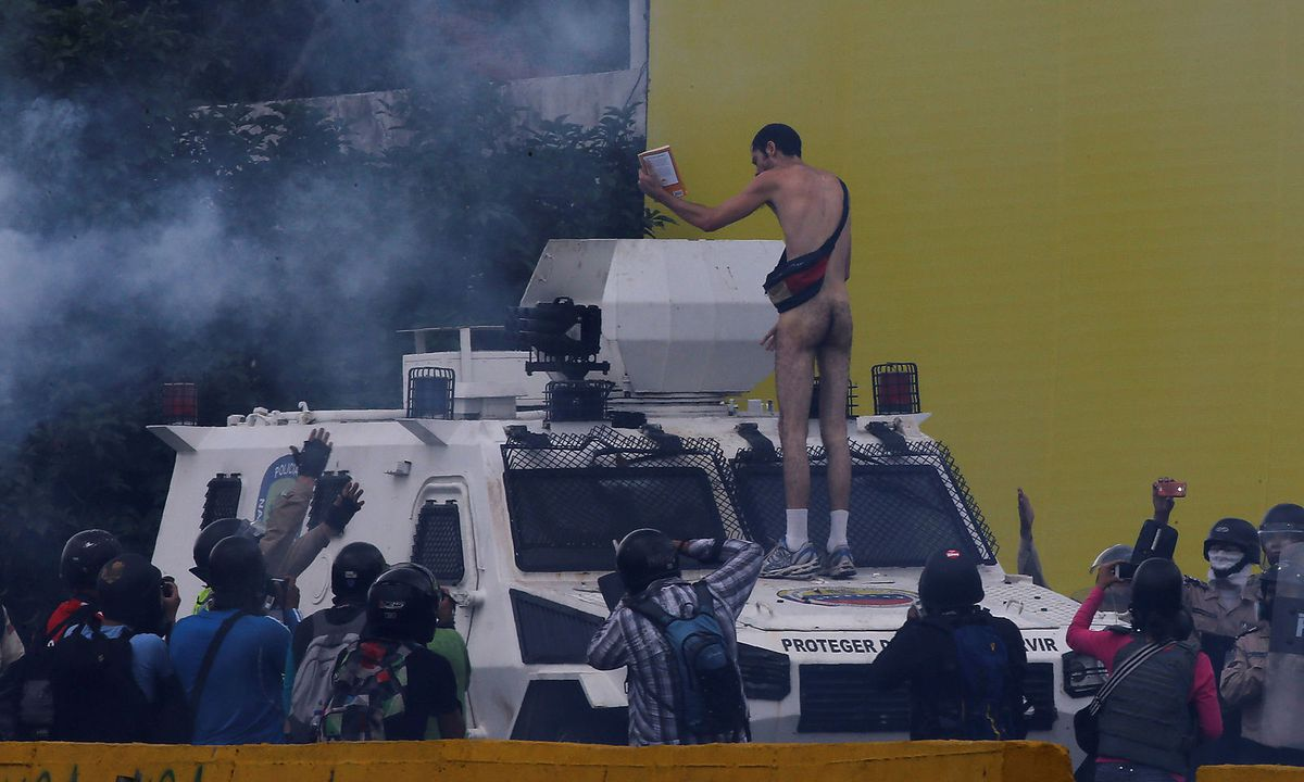 A-naked-demonstrator-stands-on-a-vehicle-of-the-national-guard-during-clashes-with-police-while-rallying-against-Venezuelas-President-Nicolas-Maduro-in-Caracas_1492770506696116_v0_h.jpg