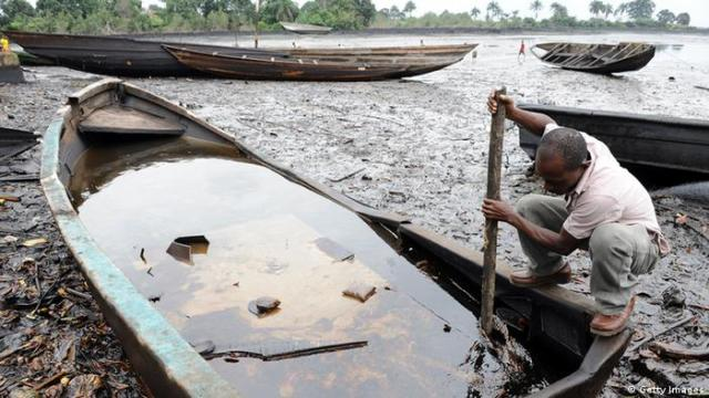 A man separating crude oil from water with a stick