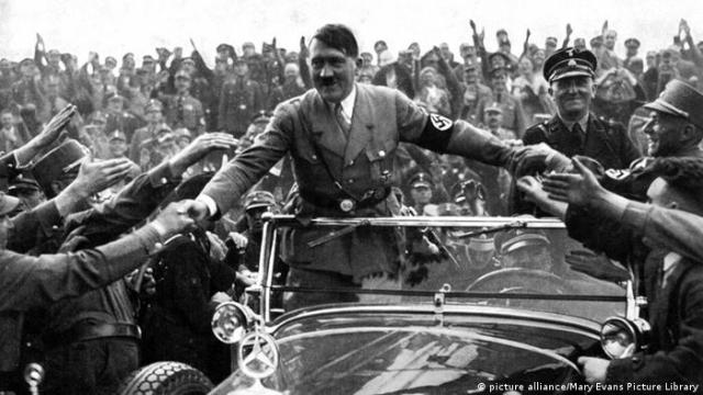 Adolf Hitler stands in a convertible as supporters reach out to him 1933 (picture alliance/Mary Evans Picture Library)