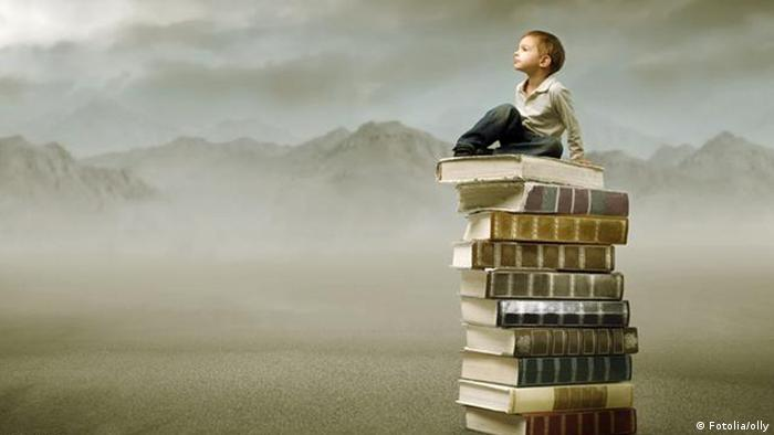Young boy sitting atop a stack of books with a mountain range in the background.