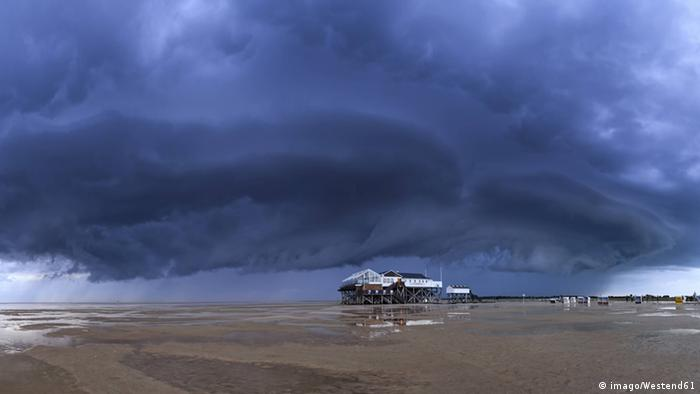 Dark storm clouds over an empty beach with a beach house on the Wadden Sea, Germany