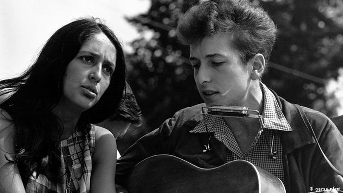 Joan Baez and Bob Dylan close together outside, Dylan with guitar and harmonica.