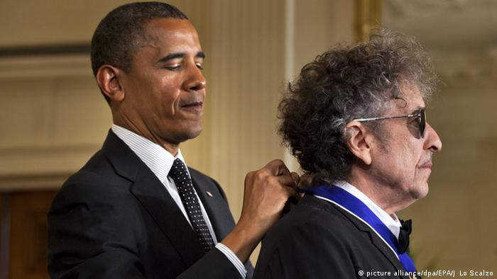 Former president clasping the medal around Bob Dylan's neck.
