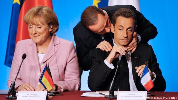 Silvio Berlusconi hugs Nicolas Sarkozy next to Angela Merkel