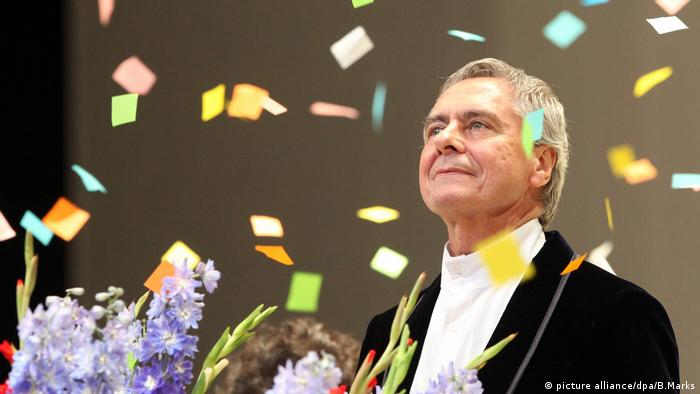 John Neumeier on stage amid falling confetti and a bouquet of flowers.