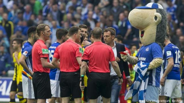 Schalke mascot Erwin holds up the red card