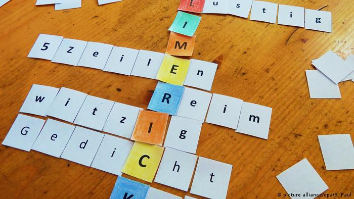 Letters laid out on the table that look like a crossword-puzzle in German.