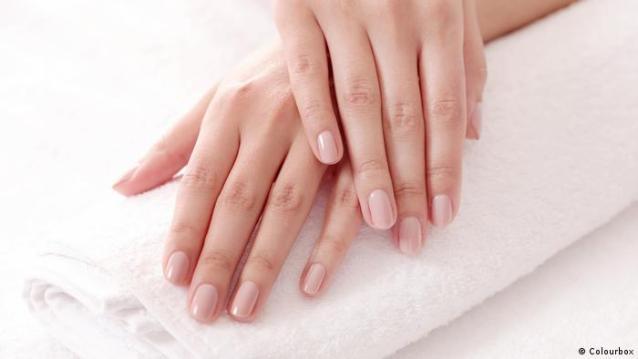 Duas mãos femininas sobre uma toalha dobrada