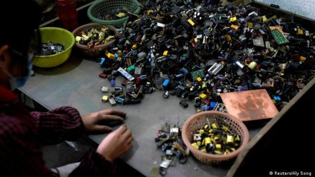 Photo: A person dismantling electronics