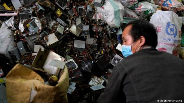 Photo: A worker wearing a mask sorts through trash