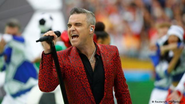 Robbie Williams singing in a red suit