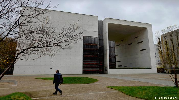 St. Canisius Church in Berlin, made of huge square blocks of concrete, with man walking in front.