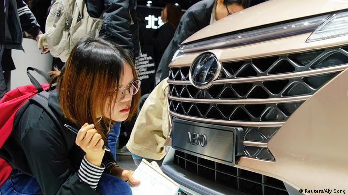 Una mujer observa la parrilla de un vehículo Hyundai.