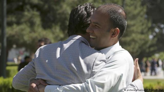 Dois homens se abraçando felizes