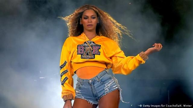 U.S. singer Beyonce Knowles performs onstage during 2018 Coachella Valley Music And Arts Festival Weekend on April 14, 2018 in Indio, California. Wind is blowing her frizzed hair and artificial smoke refracts the lights behind her.