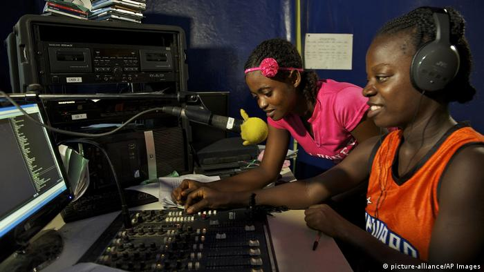 Two young women broadcast from a radio studio in Liberia