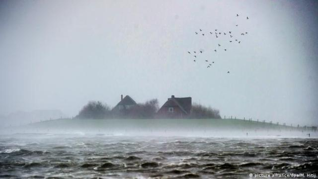 A small island with two small houses seems barely visible above the water