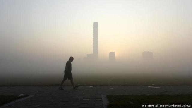 A lone man walking at dawn, smog covers the cityscape in the background