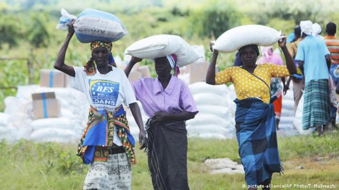 Women carry bags of corn they received as food aid, in Mudzi about 230 Kilometers northeast of the Zimbabwean capital Harare