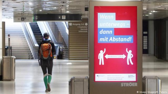 One lonely passenger walks through a Munich train station with a placard next to her demanding to obey social-distancing rules