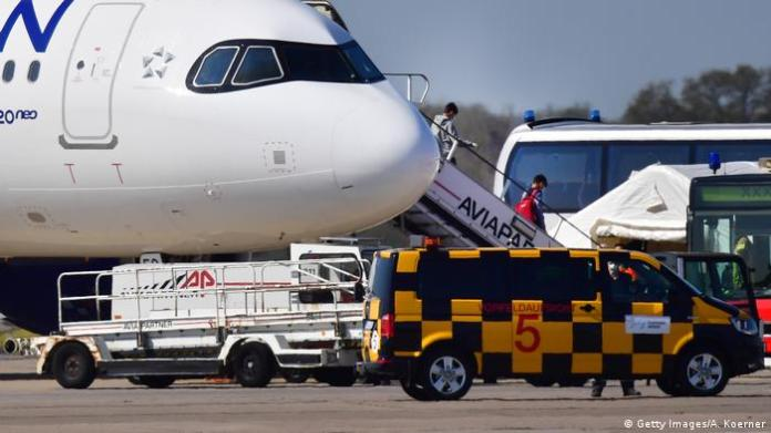 Plane at airport, two people walk down a gangway,
