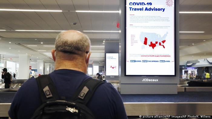 A traveler at New York's LaGuardia airport reads a COVID-19 travel advisory sign (picture-alliance/AP Images/AP Photo/K. Willens)