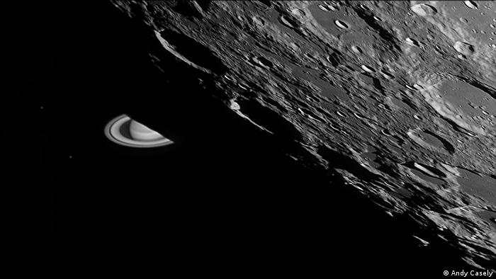 Black-and-white photography of the moon's surface with various craters, behind which the planet Saturn appears with rings (Photo: Andy Casely).