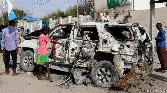 Civilians are seen near the wreckage of a car destroyed at the scene of a militant attack at the Elite Hotel in Lido beach, Mogadishu
