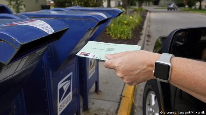 A person drops applications for mail-in ballots into a mail box in Omaha, Nebraska