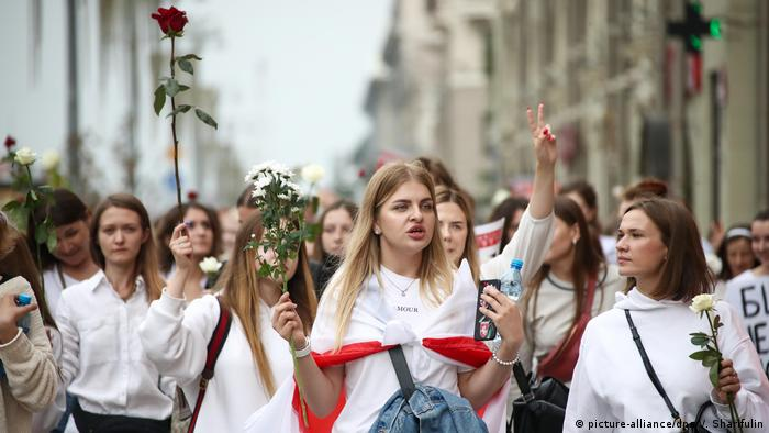 Women wearing white and bearing flowers at a Minsk protest.