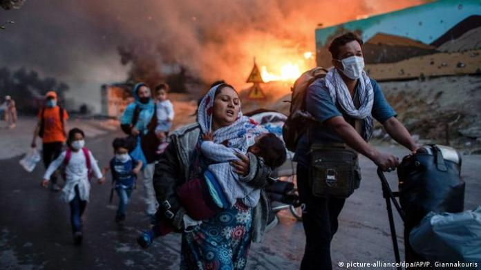 Men pushing strollers, women and kids, running down a road, fire in the background