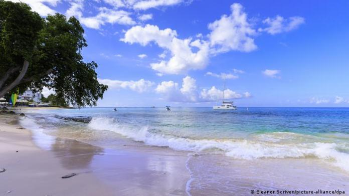 A small boat in the sea off the coast of a beach in Barbados in the Caribbean