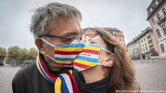 Man and woman kissing with face masks on