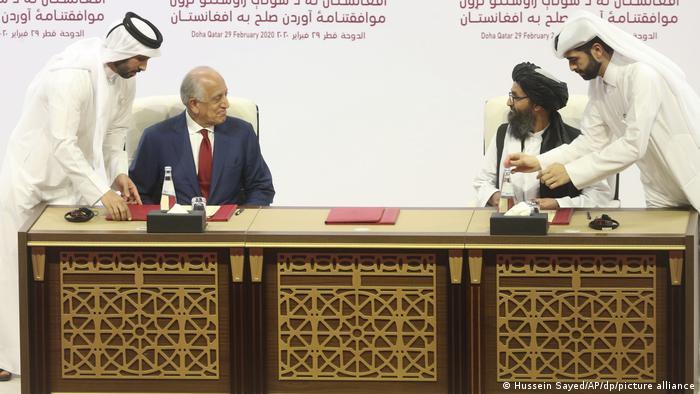 Zalmay Khalilzad (izqu.), comisionado de Estados Unidos para la paz y la reconciliación en Afganistán y Mullah Abdul Ghani Baradar, jefe de la oficina política del moviemiento talibán. Imagen en Doha del 29 de febrero de 2020.