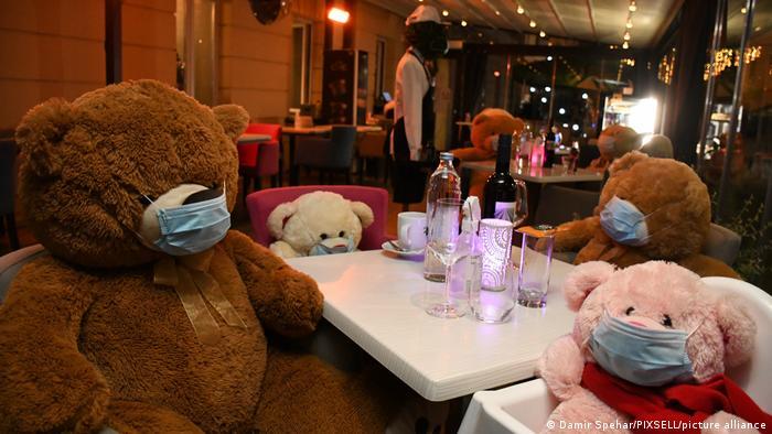 Teddybären mit Mundschutz sitzen auf der Terrasse eines kroatischen Restaurants am Tisch.