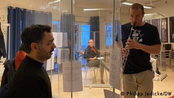 Saman Haddad sings from behind clear screen while another person plays the clarinet | Workshop 1001 Takt