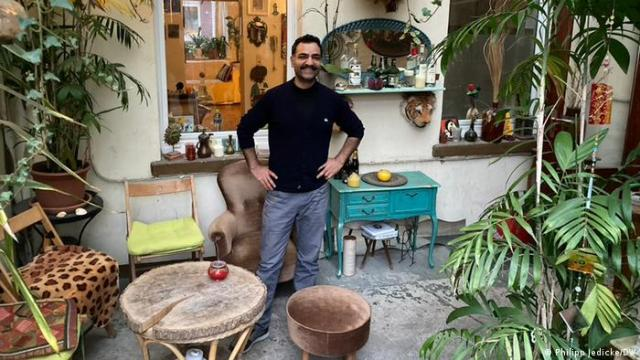 Saman Haddad stands in a lively courtyard with colorful furniture and plants | Viertelbar