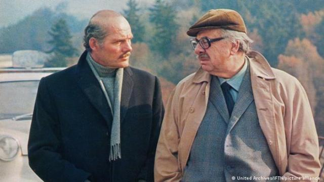 Two elderly men in suits and jackets face each other, trees in the background
