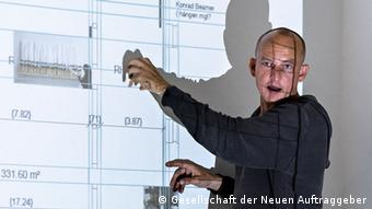 Alexander Koch stands next to a projection, pointing to it