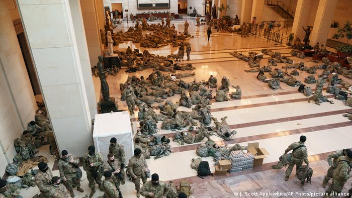 National Guard members standing, sitting, and laying down inside the US Capitol