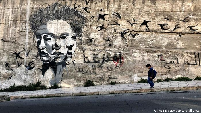 A kid walks past a mural, painted on a wall in Amman